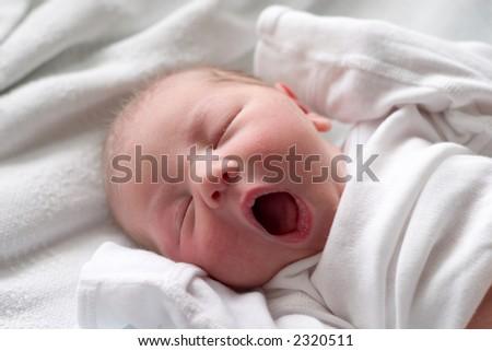 Yawning baby taking a nap - stock photo