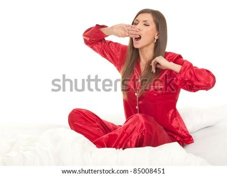 yawning beautiful young woman sleeping in white bedding, series - stock photo