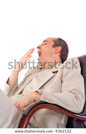 Yawning businessman siting in gray suit on black armchair - stock photo