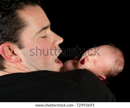 Yawning father with his 18 days old baby - stock photo