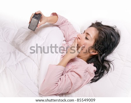 Yawning girl in bed with alarm clock