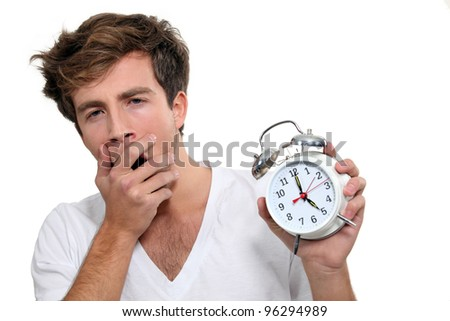 Yawning man holding alarm clock - stock photo