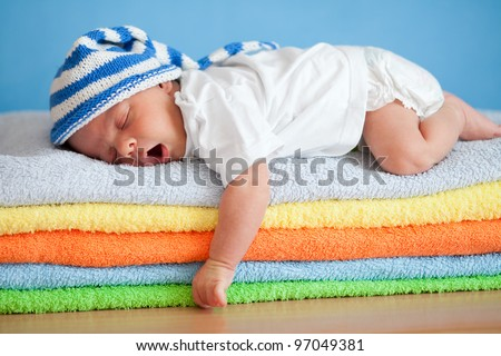 Yawning sleeping baby on colorful towels stack - stock photo