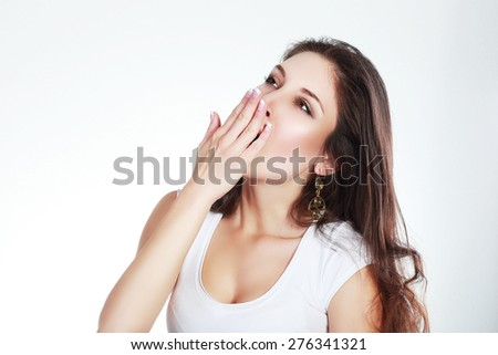 Yawning tired woman. Beautiful caucasian model isolated on white background. - stock photo