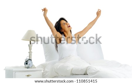 Yawning tired woman waking up in bed with alarm clock and arms out. isolated on white background - stock photo