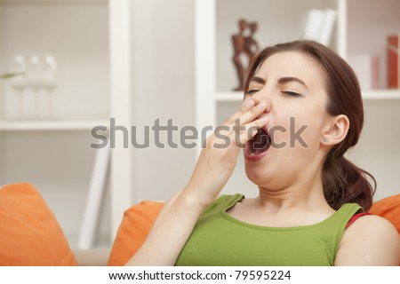 yawning woman sitting on sofa at home - stock photo