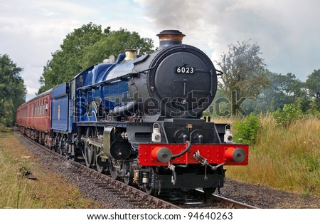 YAXLEY, ENGLAND - JULY 17: Ex GWR steam locomotive, King Edward II approaches Yaxley level crossing and station at the Mid Norfolk Railway's summer steam gala on July 17, 2011 at Yaxley. - stock photo