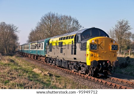 YAXLEY, ENGLAND - MARCH 19: A former British Rail class37 locomotive, in Dutch railways livery, takes passengers on short trips at the Mid Norfolk Railway spring diesel gala on March 19, 2011 at Yaxley, England.