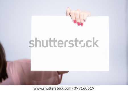Ycloseup of a young beautiful woman holding a blank for your text