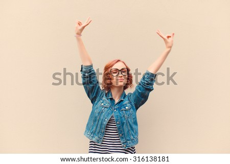 yCool hipster portrait of young stylish teen girl showing tongue, going crazy,put her hands up,shows peace sign, swag street style look,sunny positive mood and emotions,travel alone,posing on wall - stock photo