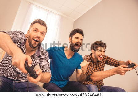 Yeah! excited happy cheerful men play video game with his friends - stock photo