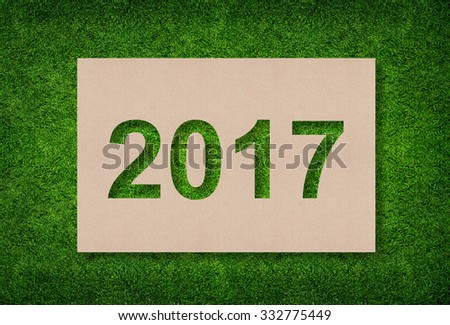 Year 2017 - Alphabet number of brown paper with green grass background.