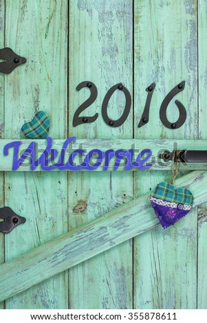 Year 2016 in black iron numbers and turquoise and purple country fabric hearts on antique rustic mint green wood door - stock photo