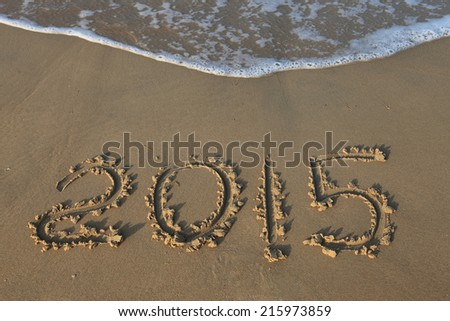 Year 2015 number written on sandy beach