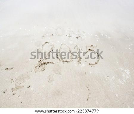 Year 2015 number written on sandy beach - stock photo