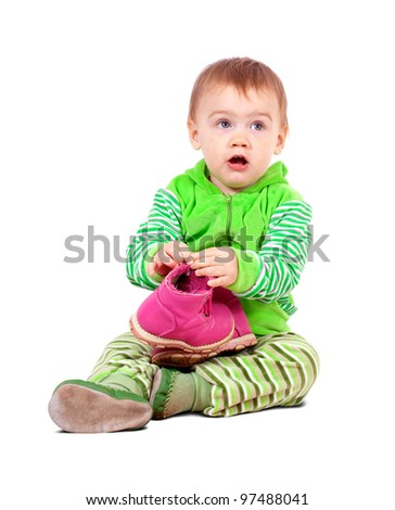 Year-old child holding shoes over white background
