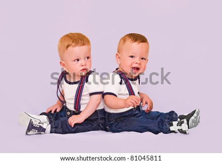 Year-old twins boys on light background - stock photo