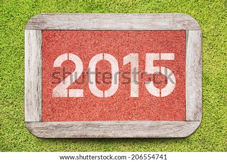 Year 2015 on running track rubber on grass background