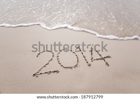 Year 2014 written in sand, on krabi beach ,Thailand