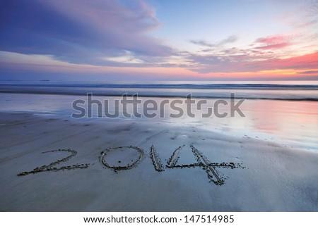 Year 2014 written on sand at Sunset - stock photo