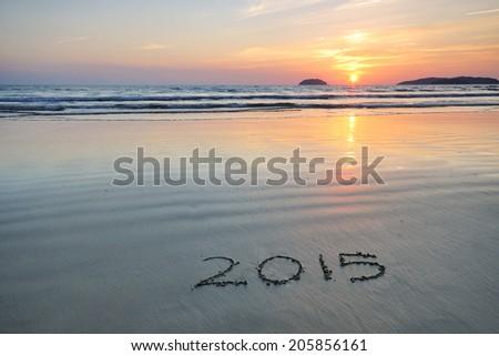 Year 2015 written on sand at Sunset  - stock photo