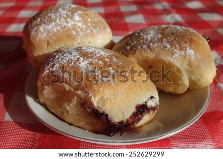 Yeast buns filled with marmalade and curd cheese sprinkle with sugar home made on red checked tablecloth horizontal - stock photo