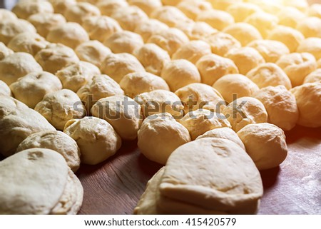 Yeast dough. Buns from dough. Dough rises on the table. Desserts making. Pies production. Baking buns. Flour products. - stock photo