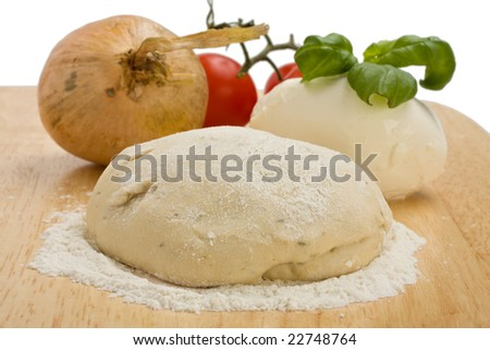 yeast dough, cheese, tomatoes and an onion on a wooden board - stock photo
