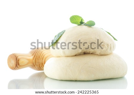 yeast dough with a wooden rolling pin on a white background - stock photo