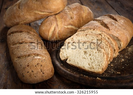 Yeast free, no knead, unleavened  healthy organic rye wheat half sliced homemade bread loaf with sesame on a round desk at wooden table