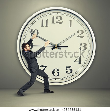 yelling businessman trying to stop a time. man and big clock over dark background - stock photo