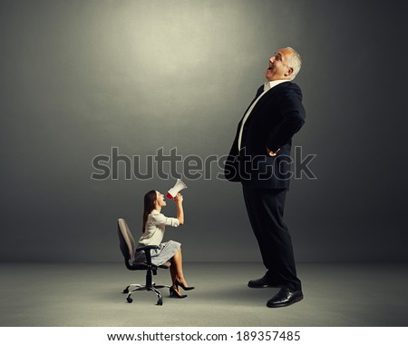 yelling woman and laughing man over dark background - stock photo