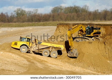 Yelloow truck and digger are working in mine - stock photo