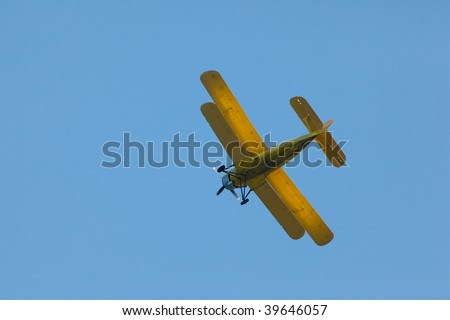 Yellow airplane (biplane) flying in a blue sky. - stock photo