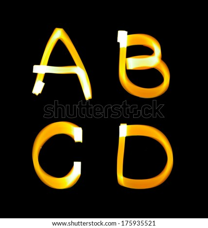yellow alphabet created with light (A, B, C, D) - stock photo