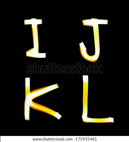 yellow alphabet created with light (I, J, K, L) - stock photo