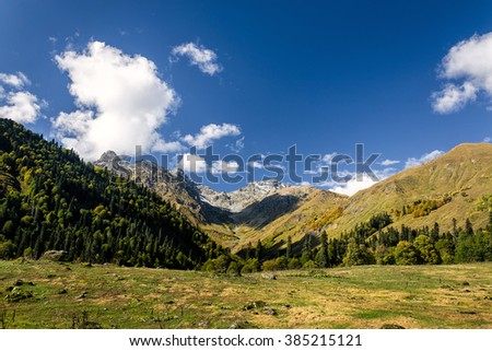 yellow alpine meadows and range of high rocky peaks in the valley of the caucasus mountains, Abkhazia Georgia - stock photo