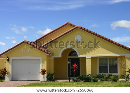 yellow american dream home against perfect blue sky - stock photo