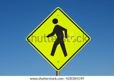 yellow and black pedestrian crossing road sign with blue sky background - stock photo