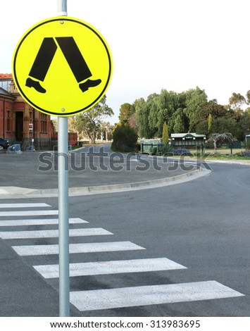 Yellow and black pedestrian crossing sign and pedestrian crossing - stock photo