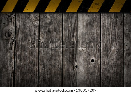 yellow and black sriped warning bar on wooden background - stock photo