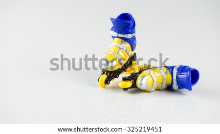 Yellow and blue color plastic roller blade or roller skate. Isolated on white background. Slightly de-focused and close-up shot. Copy space. - stock photo