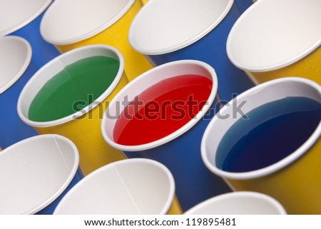 Yellow and blue cups with liquid.