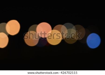 Yellow and blue defocused blurry circular night city lights glowing soft in the darkness with bright colors. They soothe, brings a positive and located in the center of the photo. - stock photo