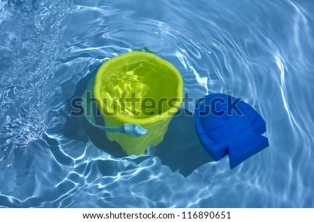 yellow and blue toys in water - stock photo