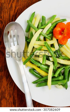 Yellow and green been side dish with a splash of color from edible nasturtium flower for that holiday buffet that can be served either warm or cold - stock photo