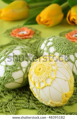 Yellow and green crochet Easter eggs and tulips - stock photo