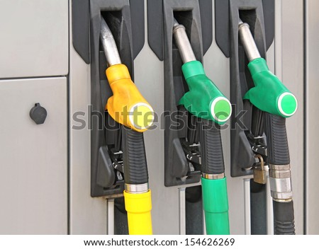 Yellow and green Pump nozzles at the gas station