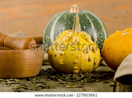 Yellow and green Pumpkins and seeds  on  a wooden table. Selective focus - stock photo