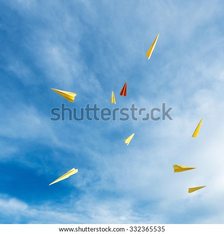 yellow and orange aircraft rocket paper hand made floating in the blue sky. - stock photo